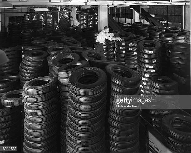 Two workers stack piles of tires in a warehouse in preparation for shipment at the Firestone Tire & Rubber Company, Akron, Ohio.