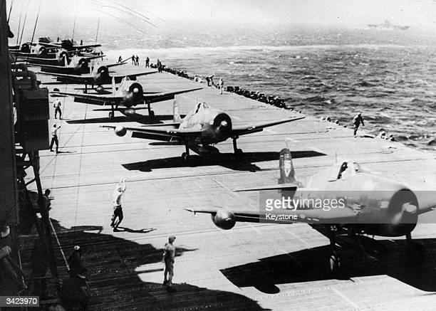 Navy Grumman Hellcats line astern in readiness for take-off against the Japanese forces in Manila. Plane handlers pass signals to pilots as the...