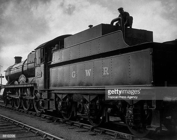 A fireman on the Great Western Railway's first oilburning locomotive attends to filling the taps on the oil container