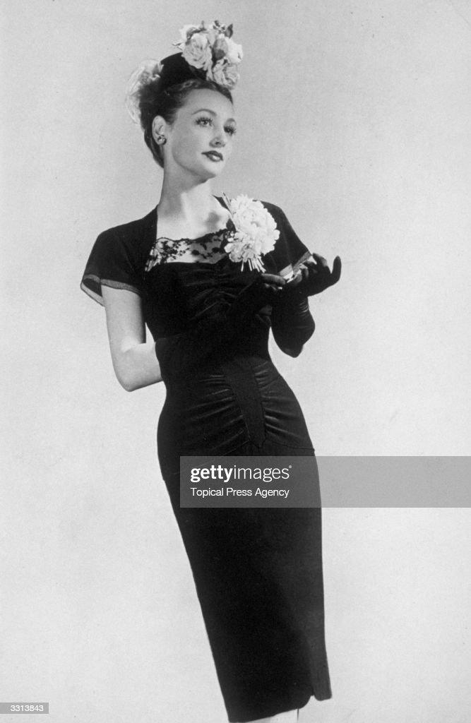 A model wearing a black lace dress, designed by Arthur Banks.