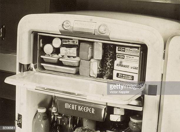 Advertisement shows a refrigerator and freezer fully stocked with frozen vegetables juice and a meatkeeping compartment 1940s