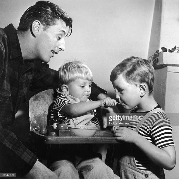 American actor Robert Mitchum watches as his younger son Christopher seated in a high chair shares his food with his older brother James