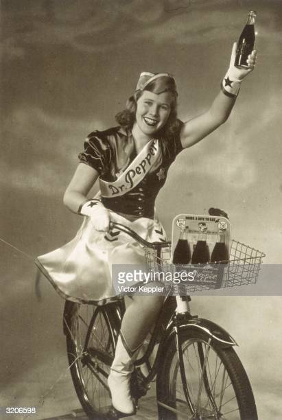 An advertisement showing a smiling young woman holding up a bottle of Dr Pepper as she rides a bicycle carrying a sixpack of the bottled soda in her...