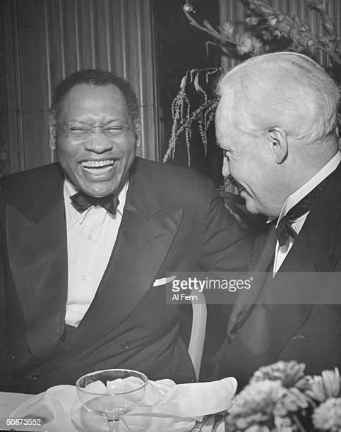 Bass singer actor Paul Robeson laughing with Carl Von Veek during party for contralto singer Marian Anderson