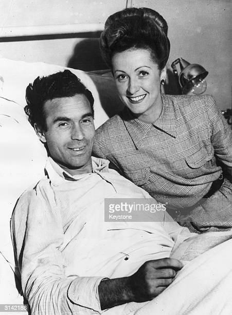 French actress Danielle Darrieux comforts her husband Dominican diplomat Porfirio Rubirosa in hospital after he was shot while driving in Paris
