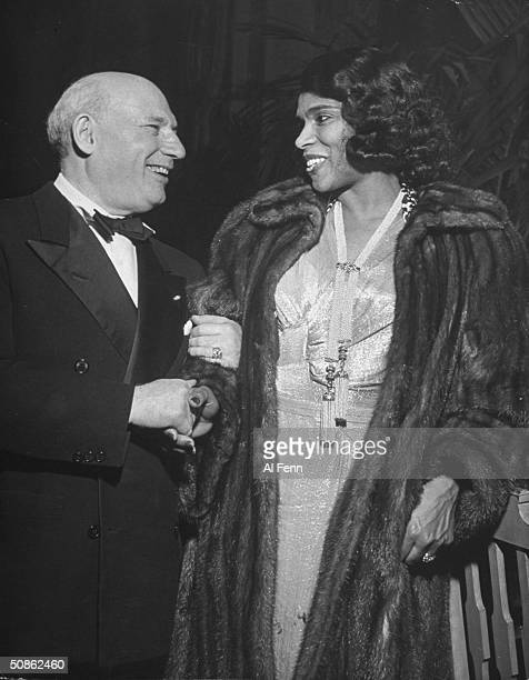 International impresario Sol Hurok saying goodnight to famed contralto singer Marian Anderson at party in her honor