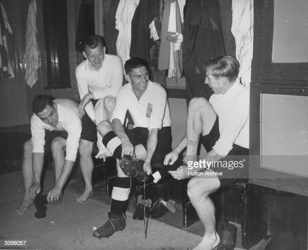 Members of Fulham FC soccer team putting their kit on in the changing room in preparation for a match