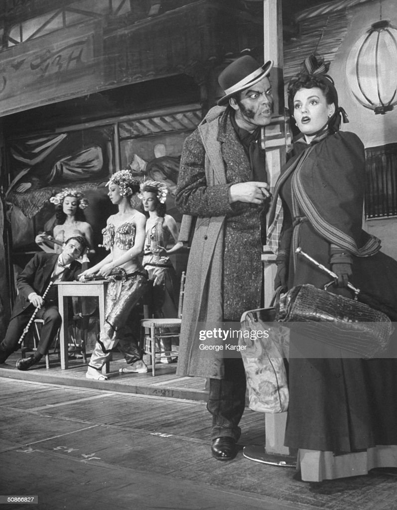 Orson Welles (2R) and Julie Warren (R) acting in a scene from his play 'Around the World.'