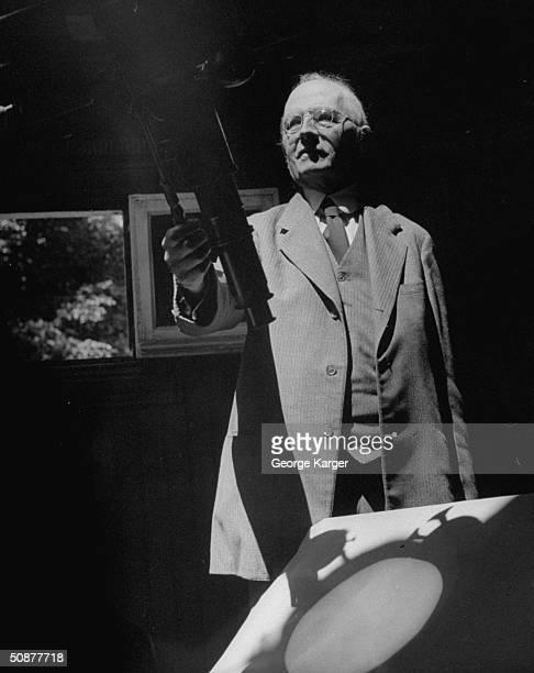 Professor Henry Norris Russell holding telescope.