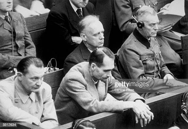 Rudolf Hess rests his hands over the bench during the Nuremberg war trials as he listens to the evidence With him are Joachim von Ribbentrop Wilhelm...