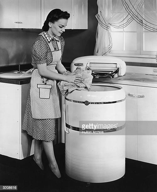 Woman wearing an apron washes her clothes in a General Electric wringer washer, in a kitchen.
