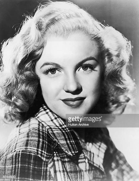 American actress Marilyn Monroe wearing a plaid flannel shirt.