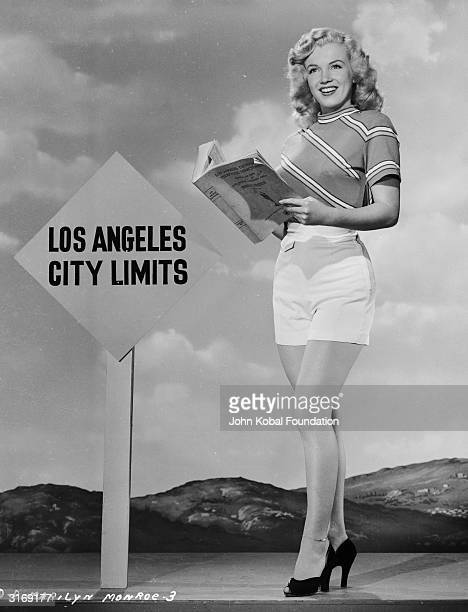 American film star Marilyn Monroe reading an LA telephone directory near the Los Angeles city limits.