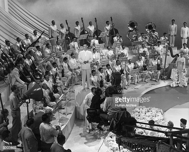 American popular singer and actor Frank Sinatra stands on a podium surrounded by a full orchestra while singing on the set of director Richard...