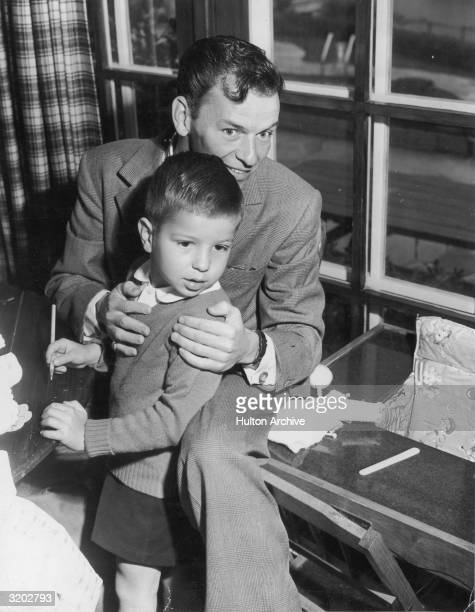 American singer and actor Frank Sinatra smiles while holding his young son Frank Jr near a window