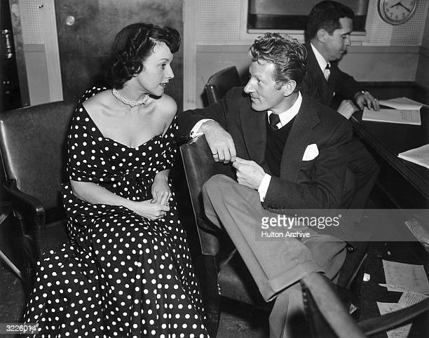 American singer Kay Starr, in a polka-dotted dress, sits talking to American actor Danny Kaye while an unidentified man reads at a desk behind them....
