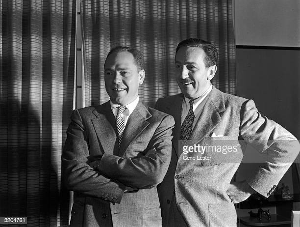 EXCLUSIVE American animator and producer Walt Disney and singer/songwriter Johnny Mercer smile while looking at something offcamera Disney stands...