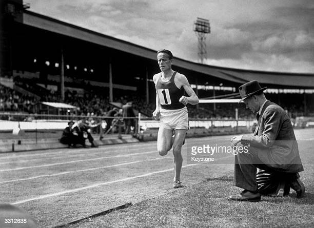 Famous Finnish athelete Paavo Nurmi sits trackside as his compatriot Viljo Heino trains for the six-mile run, in the British Games at White City,...