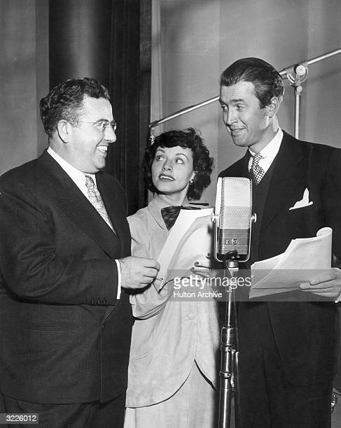 American orchestra leader John Scott Trotter, American singer Kay Starr, and American actor James Stewart smile while holding scripts behind a...