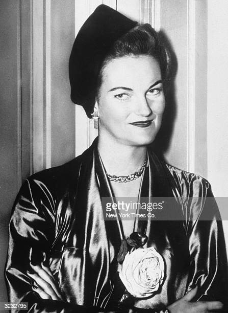 Portrait of American tobacco heiress and socialite Doris Duke wearing a satin dress with a flower on the front and a hat around the time of her...