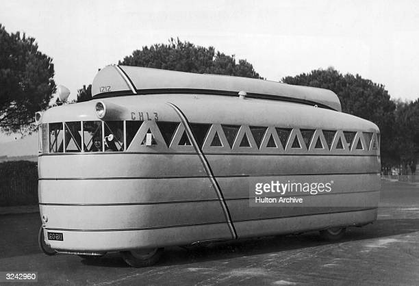Side view of a streamlined motor home designed by French inventor M Louvet carrying a canoe on top of the vehicle A member of the Louvet family sits...