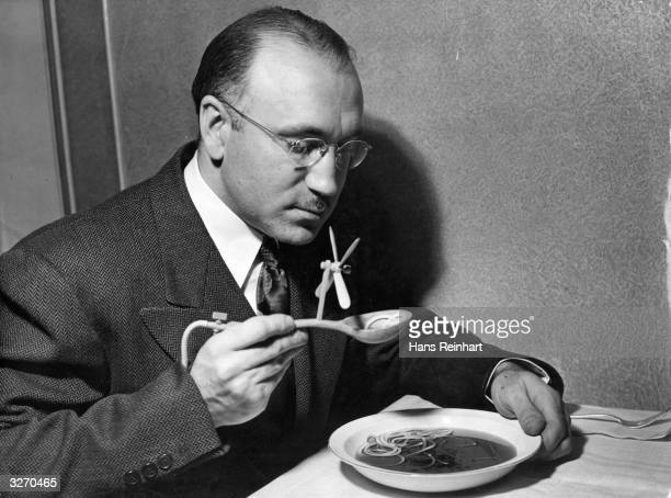 A man eating soup with a novel invention a mechanical soup spoon The device is intended for dinner parties where the hostess serves inedible soup The...