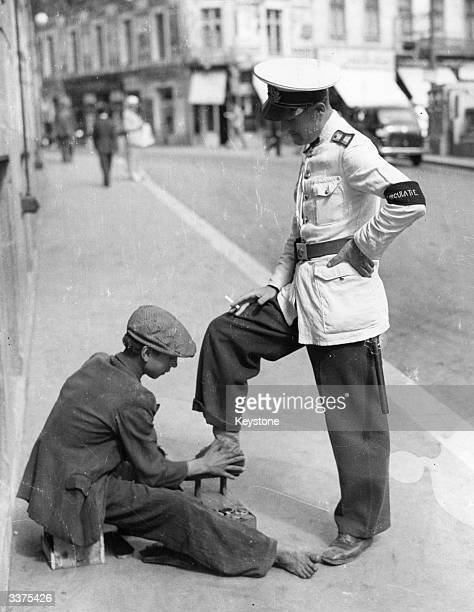 A policeman in Bucharest keeps his uniform perfect by a daily visit to the bootblack