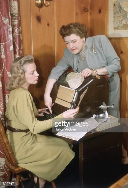 American actor June Allyson seated at an electrical typewriter for the press services being instructed on how to use it by Hollywood gossip columnist...