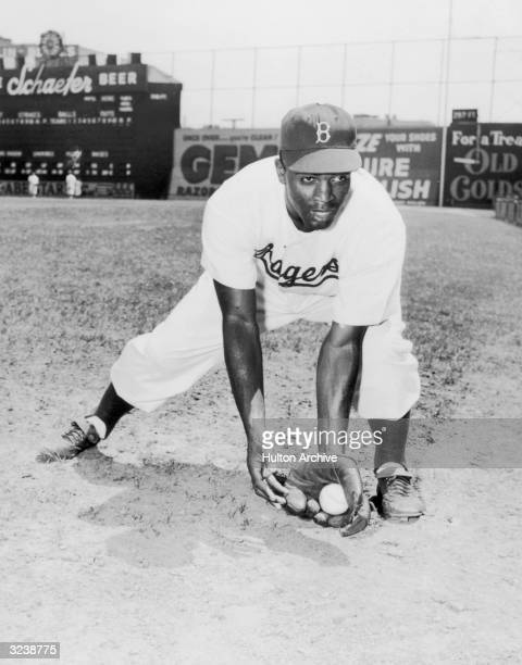 American baseball player Jackie Robinson second baseman for the Brooklyn Dodgers bends forward in the outfield with a ball in his glove