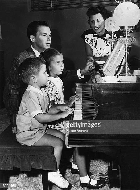American singer and actor Frank Sinatra sits at the piano with his first wife Nancy Barbato and their children Nancy and Frank Jr