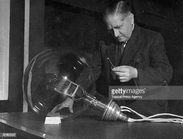 Doctor H Shaw Director of the Science Museum inspecting one of the largest light bulbs in the world a 10 kilowatt lighthouse lamp and one of the...