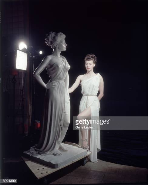 EXCLUSIVE Fulllength image of American actor Ava Gardner posing next to a statue of herself as Venus the Roman goddess of love in a promotional...