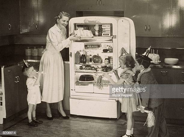 Fulllength image of a smiling woman removing a cake from a refrigerator as three young children look on excitedly in an advertisement from the late...