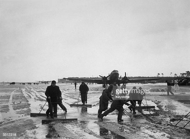 German workers clear snow throughout the night at an airfield as the Berlin Airlift is temporarily delayed by the weather