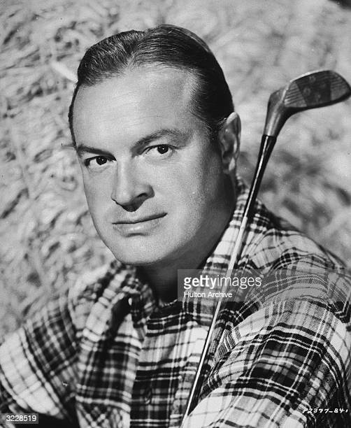 Headshot portrait of Britishborn actor and comedian Bob Hope posing in a plaid shirt with a golf club on his shoulder