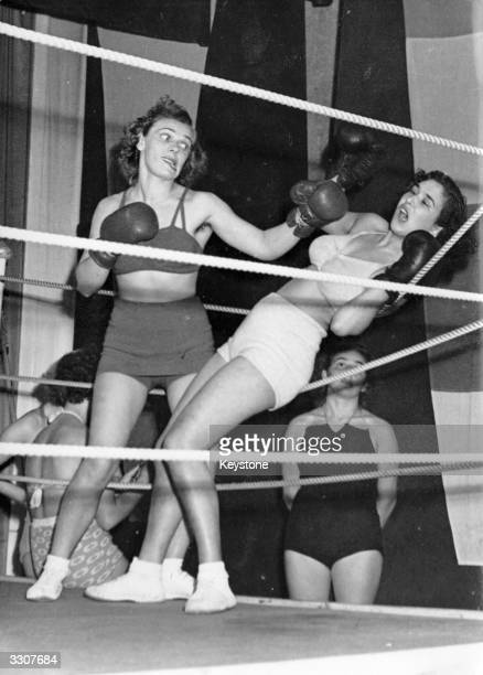 Miss Italy is knocked onto the ropes by Miss Sweden during a women's international boxing match in Stockholm