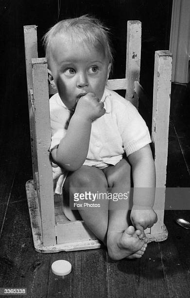 A baby sits picking his toes and sucking his thumb in an upturned stool