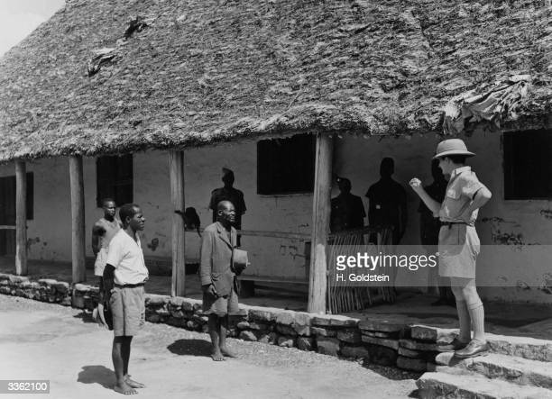 Belgian territorial agent addresses two indigenous inhabitants in the Belgian Congo.