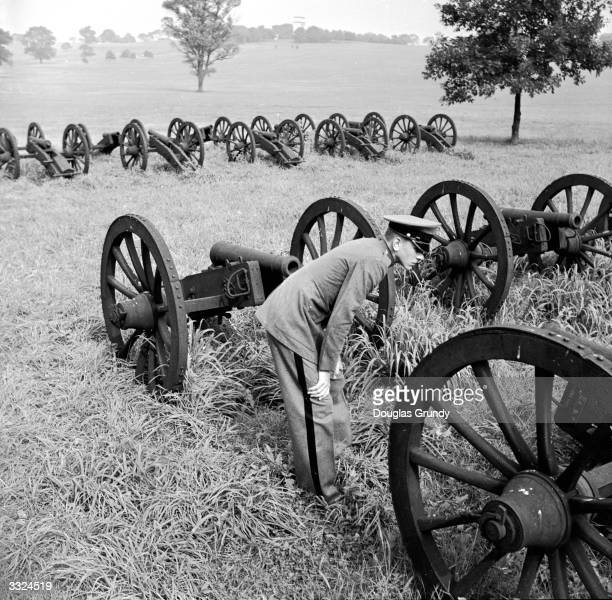 A cadet examining a Revolutionary cannon on the main Parade Grounds at Valley Forge where George Washington and the American Army camped during the...