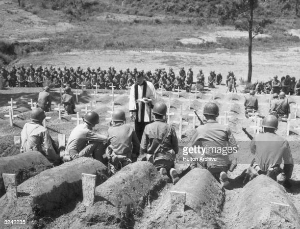 Christian minister leads a funeral service in a cemetery filled with crosses for American soldiers killed in the Korean War, Korea. American soldiers...
