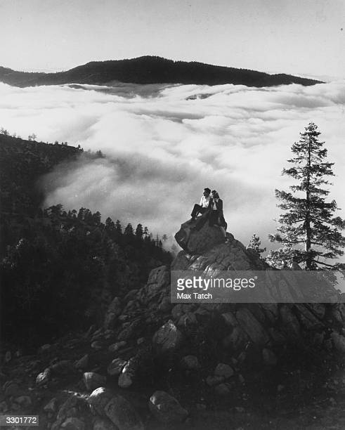 A couple sitting on a rock as clouds roll over the Angeles National Forest in California