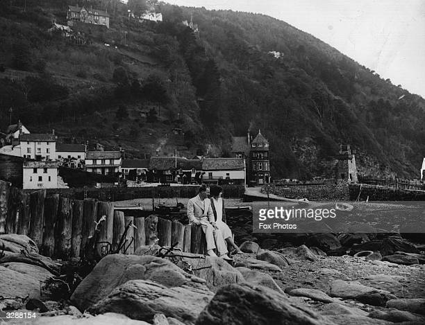 A couple sitting on a wooden fence looking out to sea at Lynmouth in Devon