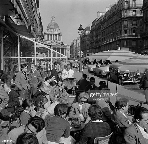 A crowded pavement cafe in a Paris street in springtime with the Pantheon in the background