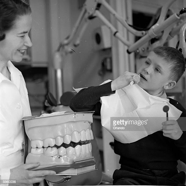 A dental technician uses a giant model of a set of dentures to explain proper brushing techniques to a young patient