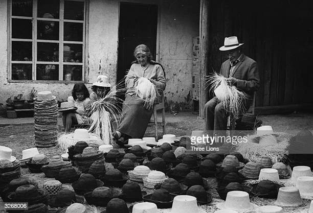 A family plaiting 'panama' hats in front of their shop in Cuenca Ecuador