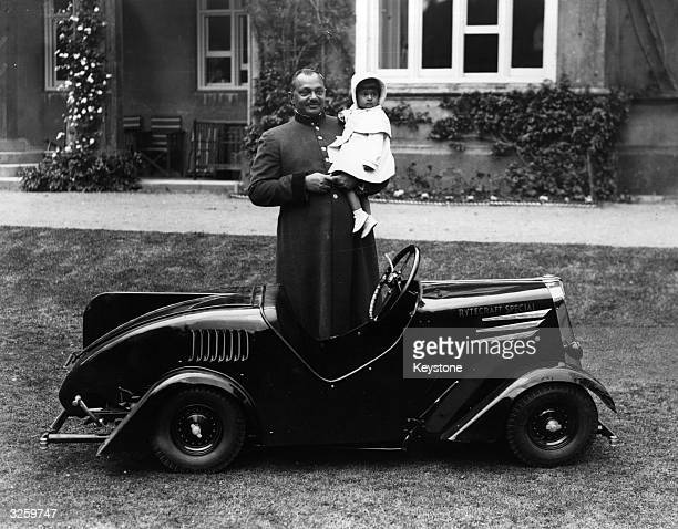 A father holding his child in a small novelty car on the lawn