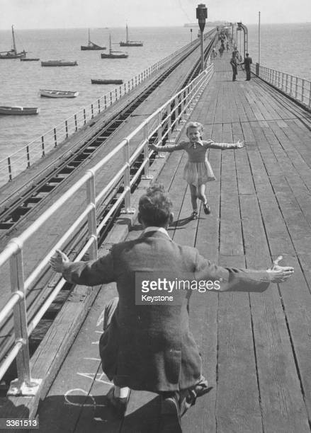A father opens his arms to receive his daughter on Southend Pier Essex