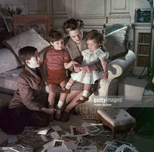 A fifties mother divides her attention up between her baby daughter and two young sons