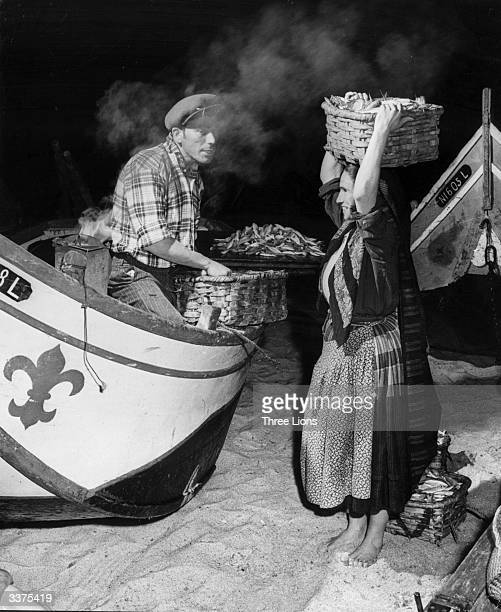 Fisherman and woman sell fresh fish from their boat in Nazare, a Portuguese fishing village.