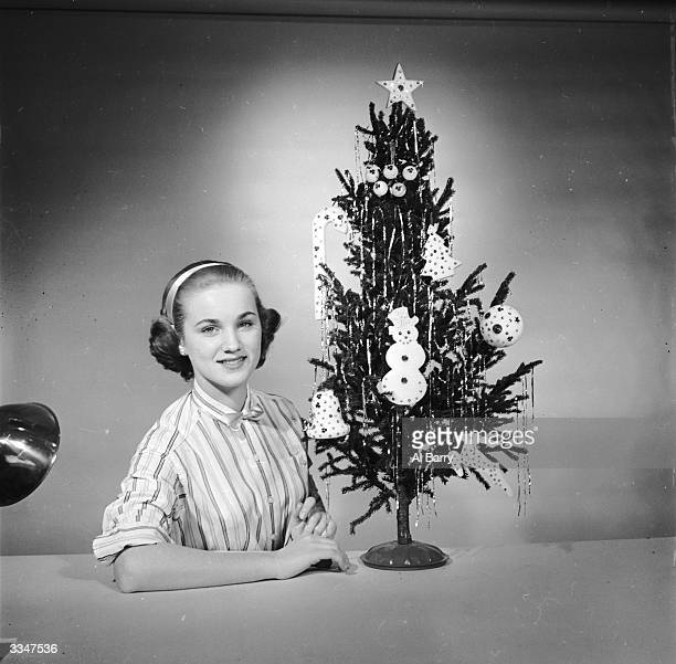 A girl sitting next to a Christmas tree